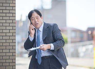 中村さんが出先で携帯電話で話しているところ
